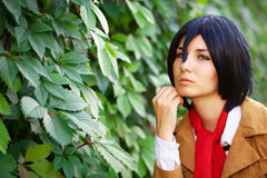 Beautiful thoughtful girl anime character near the leaves Stock Photos