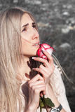 Beautiful thoughtful girl with red rose in hand Royalty Free Stock Image