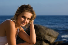 Beautiful thoughtful girl on a rocky beach Stock Image