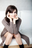 Beautiful thoughtful girl sits on a sofa Stock Photography