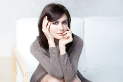 Beautiful thoughtful girl sits on a sofa Stock Photos