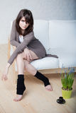 Beautiful thoughtful girl sits on a sofa Royalty Free Stock Photography