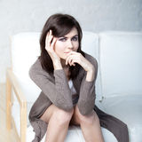 Beautiful thoughtful girl sits on a sofa Stock Images