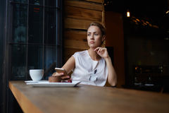 Beautiful thoughtful hipster girl using mobile phone while siting alone in modern coffee shop interior Stock Images