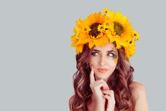 Pensive woman with floral headband looking up daydreaming stock photography