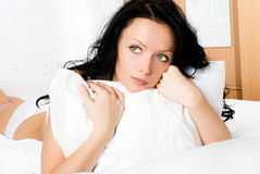 Beautiful thoughtful woman on the bed. Beautiful thoughtful brunette woman with a pillow on the bed Royalty Free Stock Photography