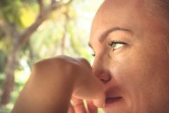 Beautiful thoughtful woman lifestyle portrait in warm colors with sunlight on woman face with tanned skin royalty free stock photos
