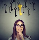 Smiling woman looking up at vintage golden key to success among many others hanging. Royalty Free Stock Images