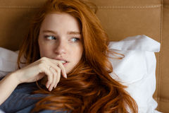 Beautiful thoughtful woman lying on the bed Stock Images