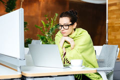 Beautiful thoughtful woman using laptop and feeling cold on workplace Royalty Free Stock Photography