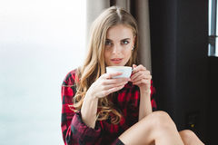 Beautiful thoughtful young woman in plaid shirt drinking coffee. In the morning Royalty Free Stock Photo