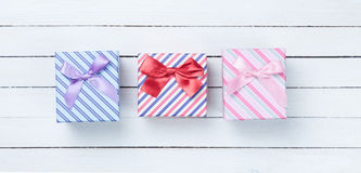 Beautiful three gifts boxes. Presents on white wooden background Stock Images