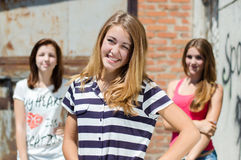 Beautiful three happy young women smiling on urban background summer day stock images
