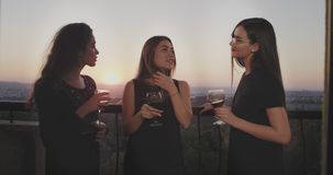 Beautiful three ladies in the top of building at the balcony have a girls party they drink some glass wine and have a stock footage