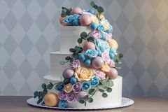 Beautiful three-tiered white wedding cake decorated with colorful flowers roses. Concept of elegant holiday desserts