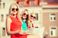 Beautiful three women with tourist map in the city Royalty Free Stock Photo