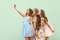 Beautiful three young adult fasion model, macking selfie, grimacing and tongue out. Green background. Royalty Free Stock Photo