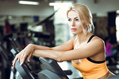 Beautiful tired blond woman on treadmill in gym after workout. Royalty Free Stock Photo