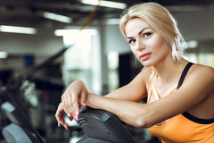 Beautiful tired blond woman on treadmill in gym after workout. Royalty Free Stock Images