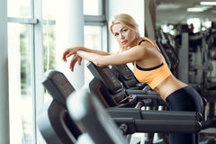 Beautiful tired blond woman on treadmill in gym after workout. Stock Image