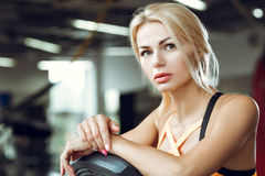 Beautiful tired blond woman on treadmill in gym after workout. Stock Photos
