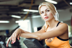 Beautiful tired blond woman on treadmill in gym after workout. Stock Photography