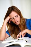 Beautiful tired blonde young girl studying Stock Photography