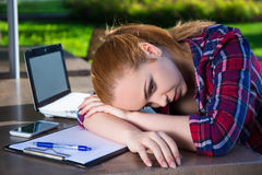 Beautiful tired teenage girl with laptop and notebook in summer Stock Image