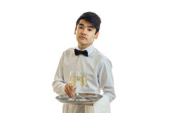 Beautiful tired young waiter holding a tray before him with a glass of champagne. Is isolated on a white background Royalty Free Stock Photo