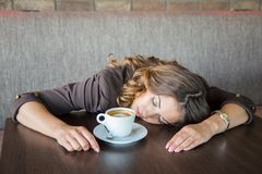 Beautiful tired young woman falling asleep while drinking coffee. at a cafe royalty free stock photos