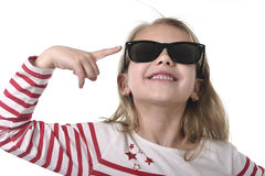 Beautiful 6 to 8 years old female child with blond hair wearing big sunglasses smiling happy and playful Stock Photo
