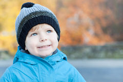 Beautiful toddler boy in blue clothes dreaming. On sunny winter day royalty free stock photo