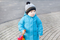 Beautiful toddler boy in blue clothes dreaming. On sunny early spring day stock image