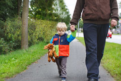 Beautiful toddler boy in colorful clothes. And his father walking together royalty free stock images
