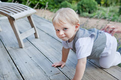 Beautiful toddler boy crawling on wooden stairs Stock Photography