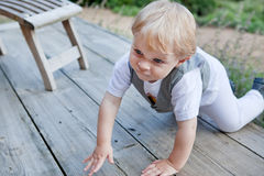 Beautiful toddler boy crawling on wooden stairs Royalty Free Stock Images