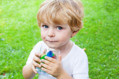 Beautiful toddler boy with glass of berry ice cubes Stock Images