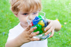 Beautiful toddler boy with glass of berry ice cubes Royalty Free Stock Photo