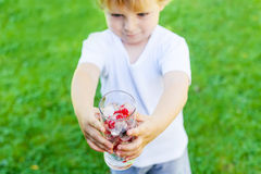 Beautiful toddler boy with glass of berry ice cubes Stock Photos