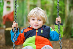 Beautiful toddler boy having fun on swing in autumn forest Royalty Free Stock Photos