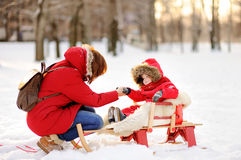 Beautiful toddler boy and his mother having fun in winter. Portrait of beautiful toddler boy and his mother having fun in winter park Stock Photo