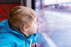 Beautiful toddler boy looking out train window outside Royalty Free Stock Photography