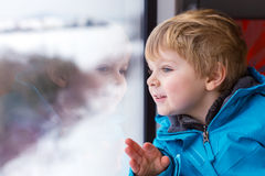Beautiful toddler boy looking out train window outside and trave. Beautiful toddler boy looking out train window outside, while it moving. Going on vacations and Royalty Free Stock Images