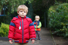 Beautiful toddler boy in red clothes with brother on background. Beautiful toddler boy in red clothes with brother on background stock photo