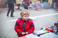Beautiful toddler boy in red clothes on flea market. Royalty Free Stock Image