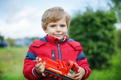 Beautiful toddler boy in red clothes with ship toy in hands. Beautiful toddler boy in red clothes with ship toy in hand stock images