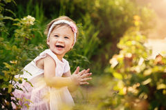 Beautiful Toddler In Garden Smiling and Clapping Stock Photography