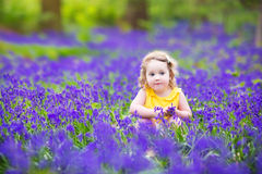 Beautiful toddler girl in bluebell flowers in spring Royalty Free Stock Photos