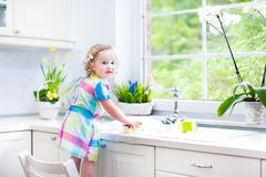 Beautiful toddler girl in colorful dress washing dishes. Cute curly toddler girl in a colorful dress washing dishes, cleaning with a sponge and playing with foam royalty free stock image