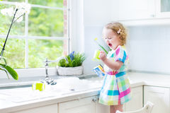 Beautiful toddler girl in colorful dress washing dishes. Cute curly toddler girl in a colorful dress washing dishes, cleaning with a sponge and playing with foam Stock Photo